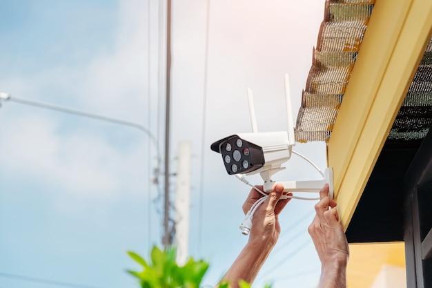 Techniker installieren eine drahtlose cctv-kamera an der vorderseite des hauses, um die sicherheit zu gewährleisten.