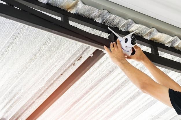 Techniker installieren eine drahtlose cctv-kamera auf dem dach.