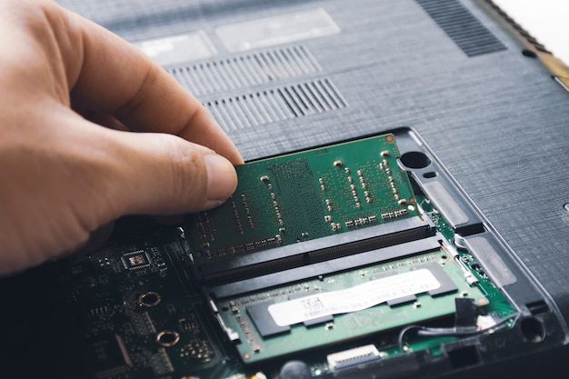 Techniker installieren neuen ram-speicher mit wahlfreiem zugriff in den speichersteckplatz auf dem laptop-motherboard