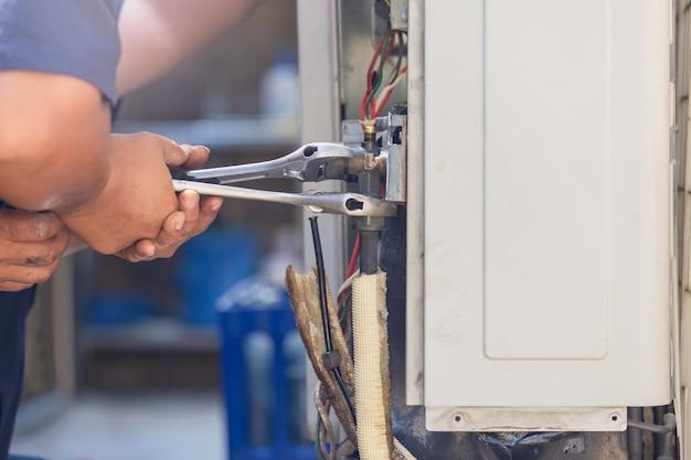 Techniker mann, der einen schraubenschlüssel verwendet, der moderne klimaanlage, wartungs- und reparaturkonzept repariert