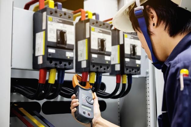 Techniker misst spannung oder strom durch clampmeter