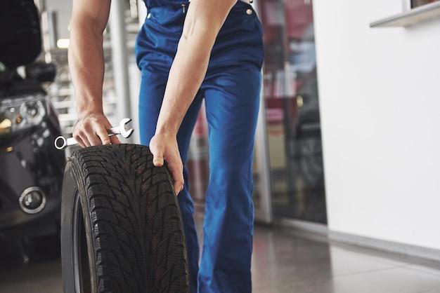 Techniker mit blauer arbeitskleidung, der einen schraubenschlüssel und einen reifen hält und dabei den daumen nach oben zeigt.