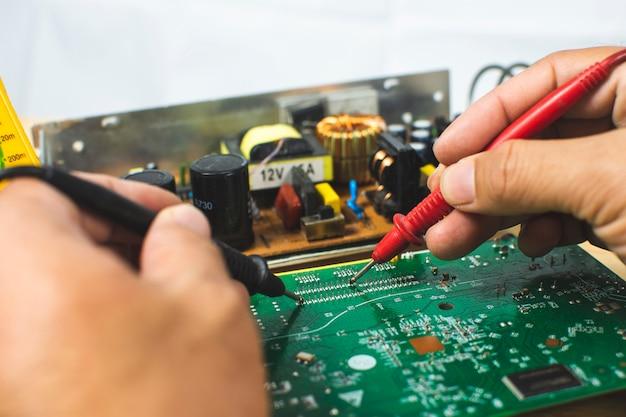 Techniker mit einem digitalmultimeter zum messen