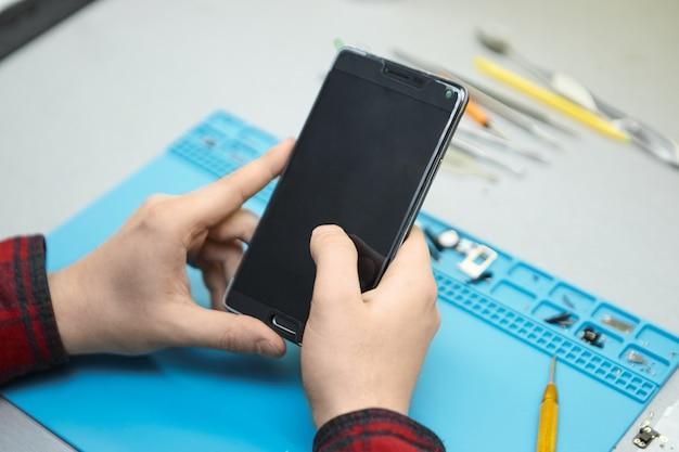 Techniker mit kariertem hemd, der an seinem arbeitsplatz sitzt und das smartphone in seinen händen einschaltet, um fehler zu finden