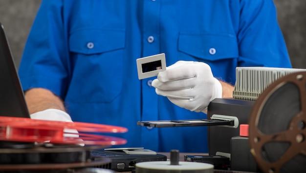 Techniker mit weißen handschuhen, die alten 35mm filmdia digitalisieren