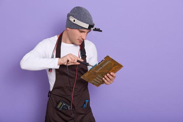 Techniker reparieren elektronische leiterplatte mit lötkolben