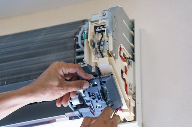 Techniker reparieren klimaanlage mit schraubendreher, installieren sie die elektrischen drähte der klimaanlage