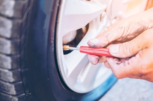 Techniker repariert flachen reifen des autos