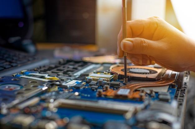 Techniker repariert kaputten laptop-notebook-computer mit schraubendreher