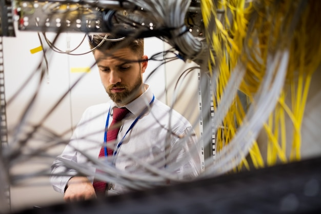 Techniker überprüft kabel in einem rack-server