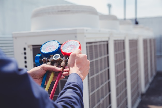 Techniker überprüft klimaanlage, messende ausrüstung für das füllen von klimaanlagen.