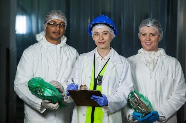 Techniker und metzger halten verpacktes fleisch und zwischenablage