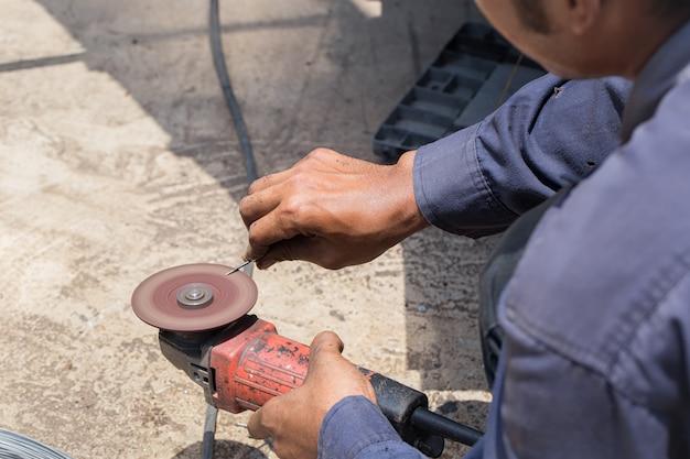Techniker verwenden schleifmaschinen für die arbeit an nägeln an einem heißen tag.