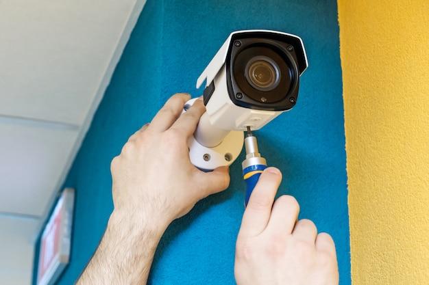 Technikerarbeitskraft, die videoüberwachungskamera installiert