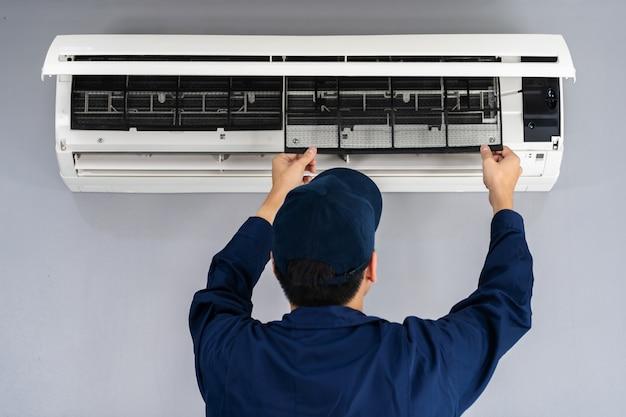 Technikerdienst, der den luftfilter der klimaanlage zur reinigung entfernt