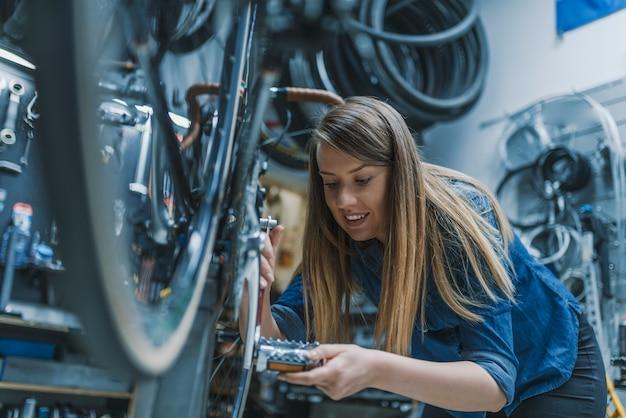 Technikerfrauenfestlegungsfahrrad in der reparaturwerkstatt