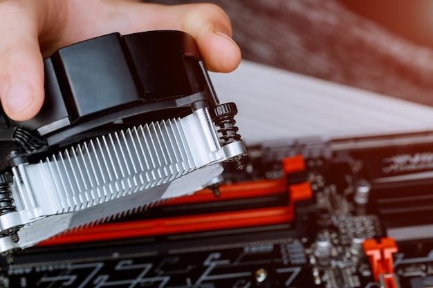 Technikerhände, die cpu-kühlerlüfter auf einem computer-pc-motherboard mit gpu-anlagen installieren.