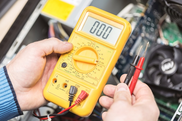 Technikerhände halten voltmeter über computermotherboard,