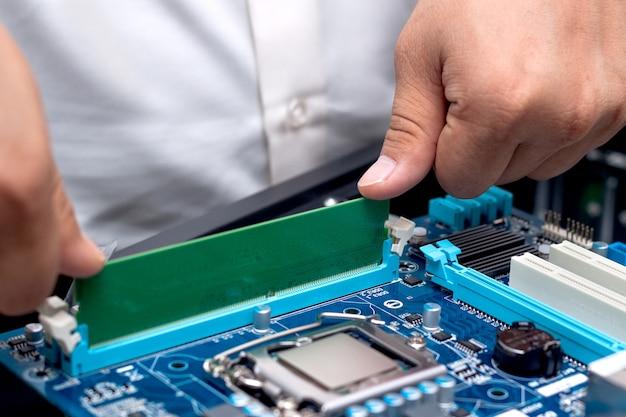 Technikerhände installieren benutzerspeicher auf einer hauptplatine eines computers