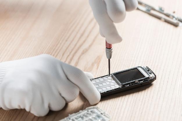 Technikerhand, die mobiltelefon auf hölzernem hintergrund repariert