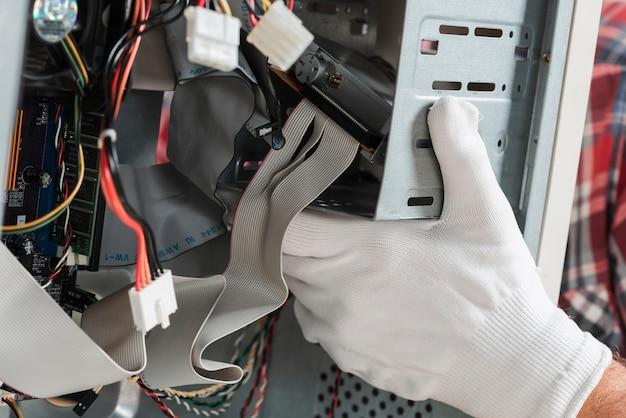 Technikerhand mit den handschuhen, die computer reparieren