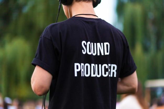 Technikerkerl in den kopfhörern und im t-shirt mit der aufschrift