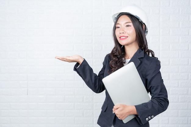 Technikfrau, die ein unterschiedliches notizbuch, weiße backsteinmauer hält machte gesten mit gebärdensprache.