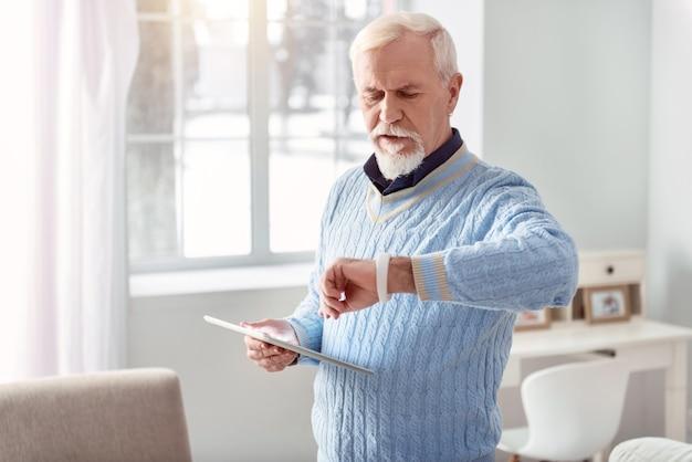 Technikliebhaber. charmanter älterer mann, der eine tafel hält und seine intelligente uhr schaut, während er in der mitte des wohnzimmers steht