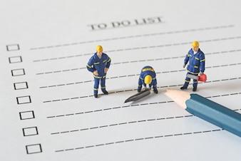Technische Miniaturfiguren Menschen auf mit einem gebrochenen Stift Liste tun