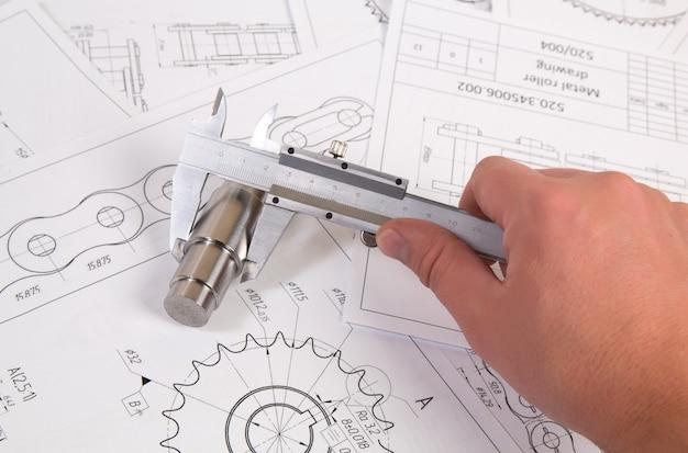 Technische zeichnung, bremssattel und antriebsrollenkette. ingenieurwesen, technologie und metallverarbeitung. schiebermessung des details der industriekette.