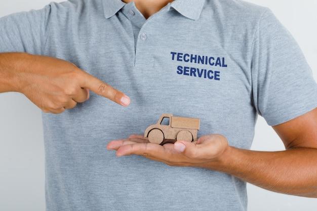 Technischer servicemann, der hölzernes spielzeugauto im grauen t-shirt zeigt