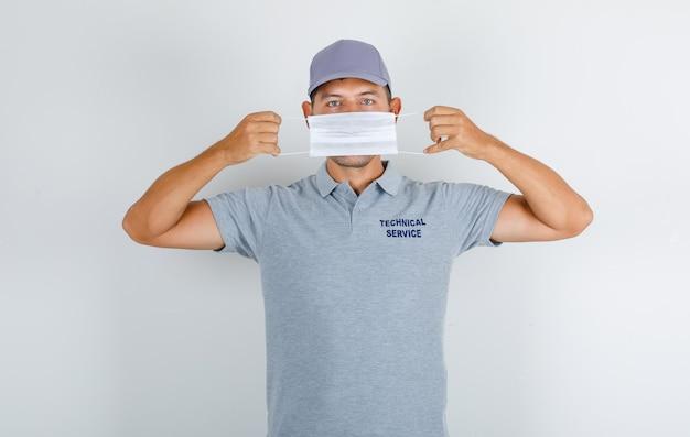 Technischer servicemann, der medizinische maske im grauen t-shirt mit kappe trägt und vorsichtig schaut