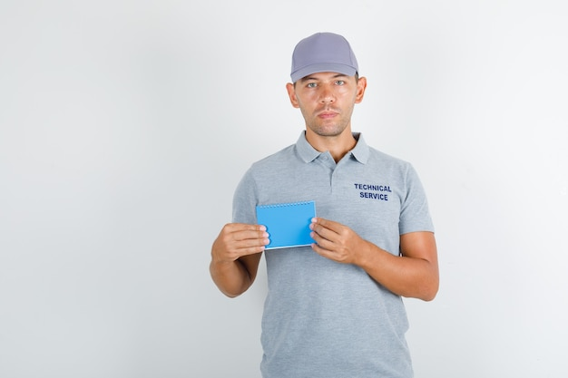 Technischer servicemann, der mini-notizbuch im grauen t-shirt mit kappe hält
