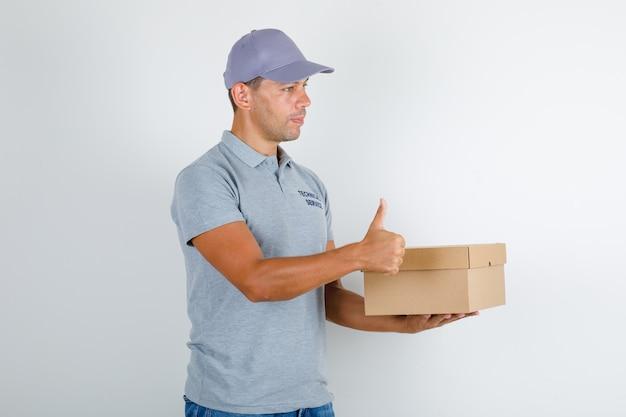 Technischer servicemann, der pappkarton mit daumen oben im grauen t-shirt mit kappe hält