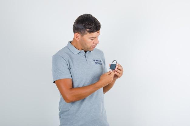 Technischer servicemann, der schloss mit werkzeugkasten hält und beschäftigt schaut