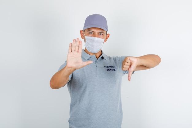 Technischer servicemann, der stoppschild mit daumen nach unten im grauen t-shirt mit kappe tut