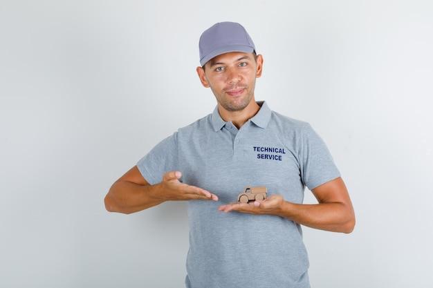 Technischer servicemann im grauen t-shirt mit kappe, die hölzernes spielzeugauto zeigt