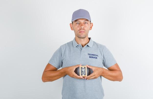 Technischer servicemann im grauen t-shirt mit kappe, die sanduhr hält und pünktlich aussieht