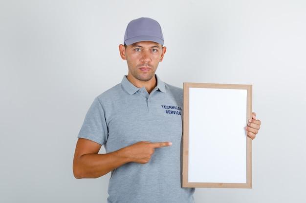 Technischer servicemann im grauen t-shirt mit kappe, die weiße tafel zeigt