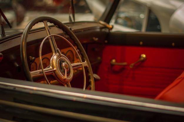 Technisches museum. altes retro- autolenkrad, roter innenraum.