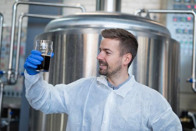 Technologe, der durch ein glas getränkeprodukt schaut und qualität prüft
