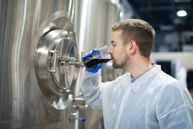 Technologe, der ein glas getränkeprodukt probiert und die qualität überprüft