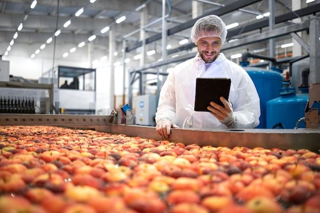 Technologe, der in der lebensmittelverarbeitungsfabrik steht und qualität der apfelfrucht prüft.