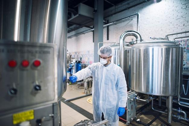 Technologe, der maschine in produktionsanlage steuert