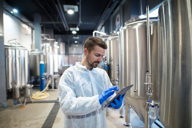 Technologe experte mit tablet-computer in der produktionslinie der lebensmittelfabrik