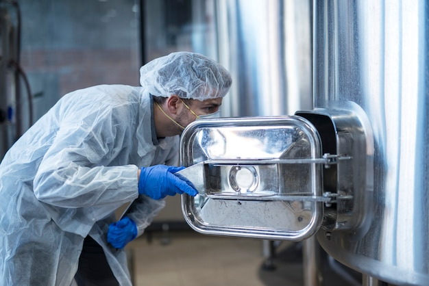 Technologe im weißen anzug, der in maschine in der produktionslinie der lebensmittelfabrik schaut