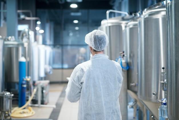 Technologe im weißen schutzanzug, der durch die produktionslinie der lebensmittelfabrik geht und qualität überprüft