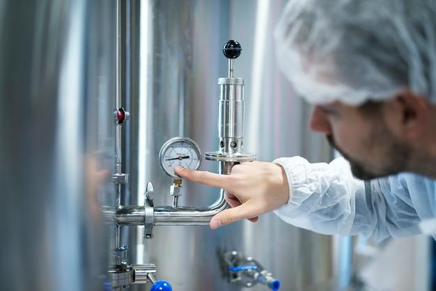Technologe im weißen schutzanzug prüft den druck auf dem manometer der industriemaschine im werk