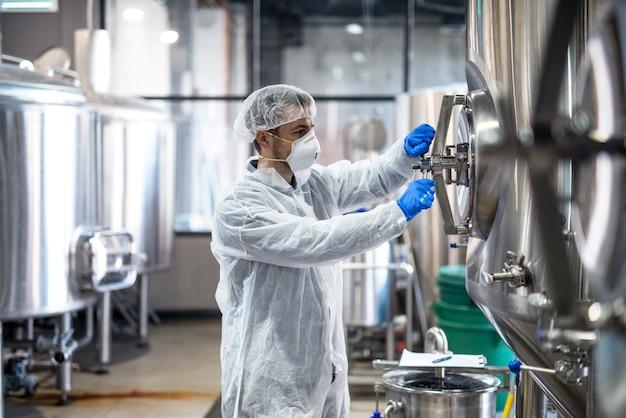 Technologe in schutzuniform mit haarnetzmaskenbrille und handschuhen, die den industrietankbehälter schließen