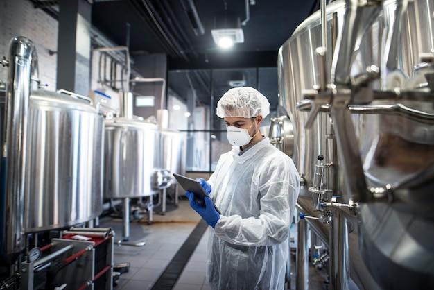 Technologe in weißer schutzkleidung, der die produktion auf seinem tablet überprüft